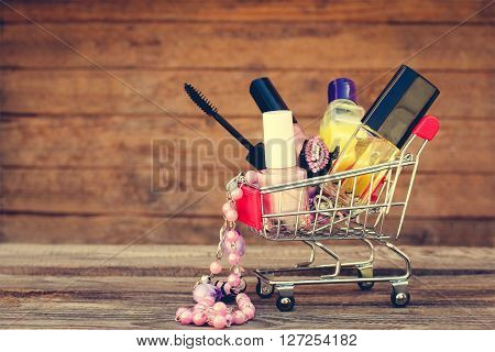 Shopping cart with cosmetics, beads, hair clip on the old wood background. Toned image.