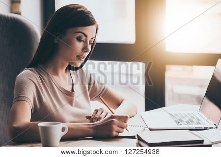 New business plan. Close-up of young beautiful woman writing in notebook while sitting in chair in front of window