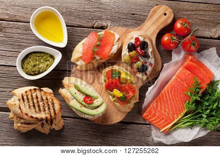 Toast sandwiches with avocado, tomatoes, salmon and olives on wooden background. Top view