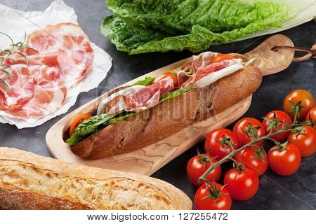 Ciabatta sandwich with romaine salad, prosciutto and mozzarella cheese over stone background