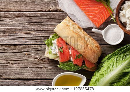 Sandwich with salmon and cheese on wooden background. Top view with copy space