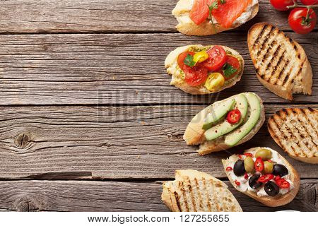 Toast sandwiches with avocado, tomatoes, salmon and olives on wooden background. Top view with copy space