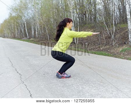 Young Woman Squat Outdoors In Nature