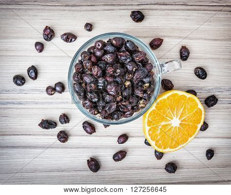 Dried rose hips in the glass bowl and sliced orange on the wooden background. Healthy lifestyle.