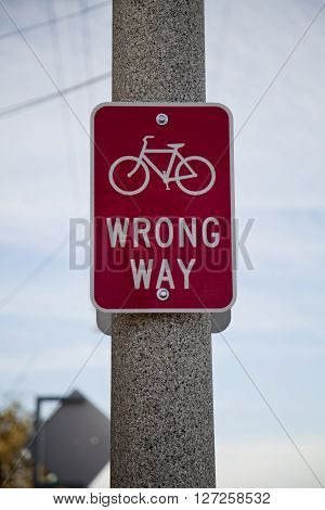 A red cyclists wrong way sign on a lamp post