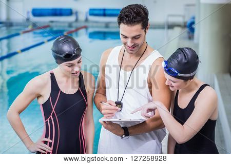Smiling trainer showing clipboard at swimmers at the leisure center