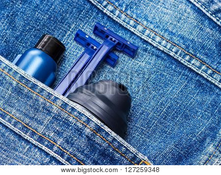 Men's cosmetics. Shaving foam, disposable razors and aftershave lotion in jeans pocket. Basic skin care cosmetic products and accessories for men. Toiletry and cosmetic travel kit