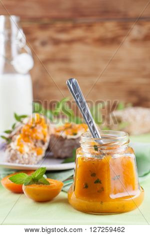 Jar with spicy apricot jam with mint. Bread and milk in the background