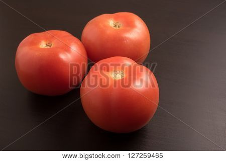 fresh three tomatoes on the black table