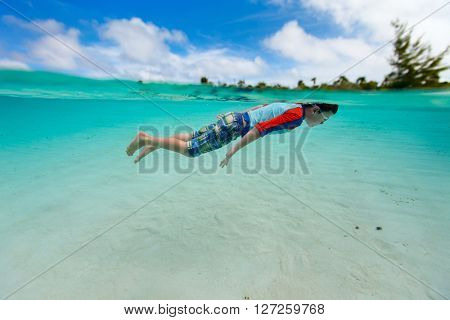 Split of above and underwater photo of cute little boy swimming in ocean