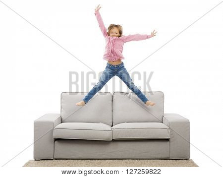 Cute blonde girl jumping over the sofa