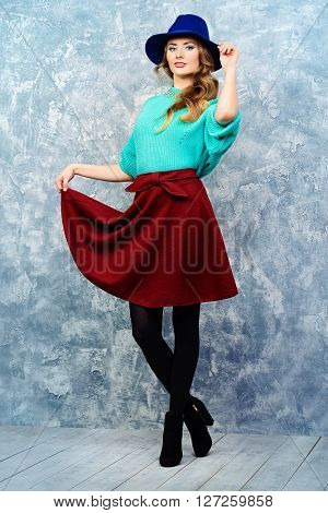 Cheerful pretty woman in a bright casual sweater, skirt  and a felt hat. Beauty, fashion. Bright make-up, cosmetics. Full length portrait.