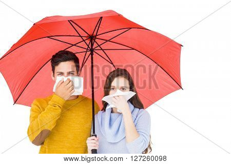 Couple blowing their noses under an umbrella on white background