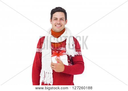 Handsome man with winter clothes holding gift box on white background