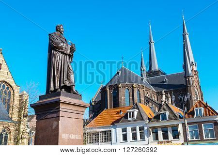 Delft, Netherlands - April 8, 2016: Statue of Hugo Grotius, traditional dutch houses in downtown of popular Holland destination
