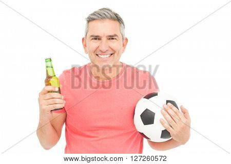 Happy man holding a soccer ball and a beer on white background