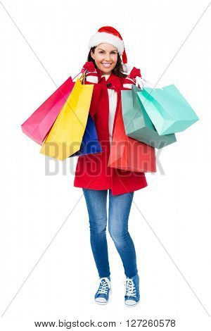 Beautiful brunette with santa hat holding shopping bags on white background