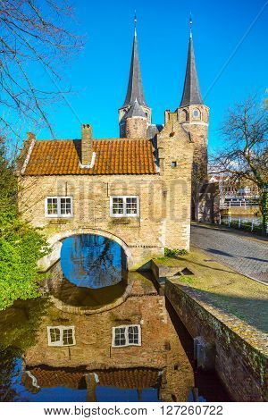 Colorful Oostpoort or Eastern Gate domes, canal and house reflection, Delft, Netherlands, Holland against blue sky