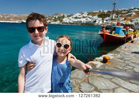 Kids brother and sister making selfie with a stick at Mykonos island, Greece