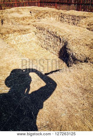 Photographer's shadow and haystacks. Straw bales. Silhouette of man. Rural scene. Photography theme. Light and shadow.