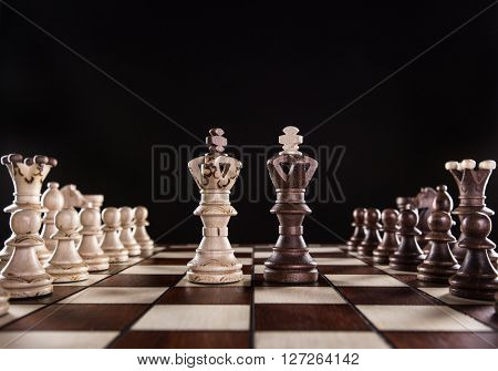 Chess pieces on dark background, close-up.
