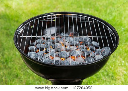 Empty grill with red-hot briquettes, close-up.