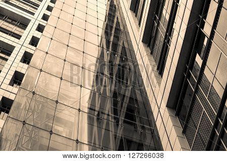 Sepia trendy image of business center building made of steel and glass. Finance center sepia conceptual background.