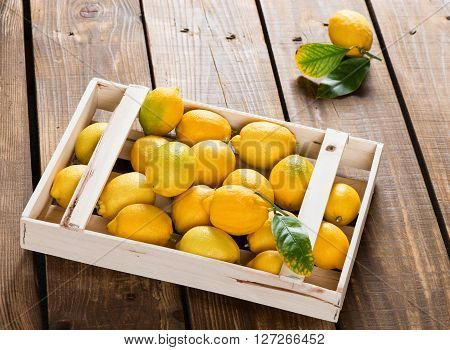 Lemons with green leaves in crate on rustic wooden table.
