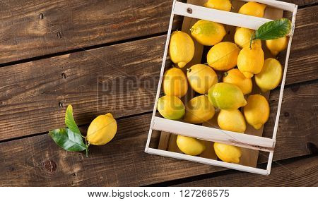 Top view of fresh lemons in crate on wooden table with space for text.