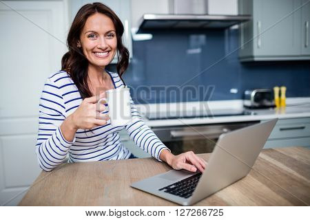 Portrait of smiling young woman working on laptop while holding coffee mug at table in kitchen