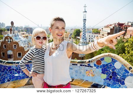 Happy Mother Pointing On Something To Baby At Park Guell