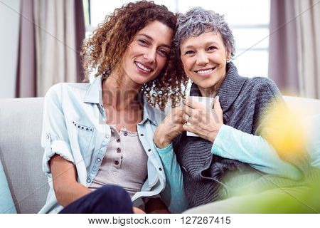 Portrait of smiling mother and daughter with coffee mug while sitting at home