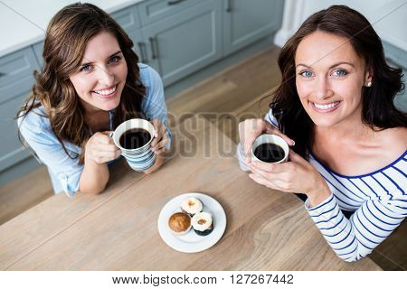 High angle portrait of female friends holding coffee mugs while sitting at table in kitchen