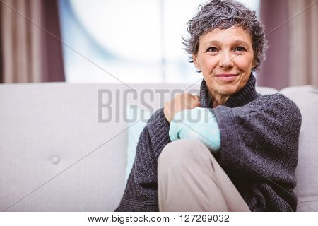 Portrait of smiling mature woman sitting on sofa at home