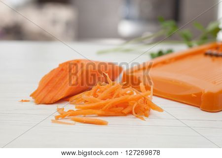 half carrot, grated carrots and grater,food ingredients