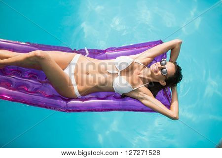 High angle view of beautiful woman relaxing on inflatable raft at swimming pool
