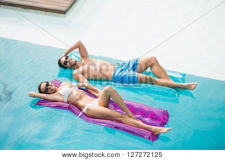High angle view of smiling couple relaxing on inflatable raft at swimming pool
