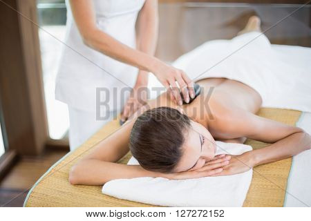 Woman receiving stone massage from female masseur at health spa