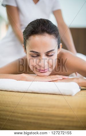 Close-up young woman with eyes closed while receiving massage at health spa
