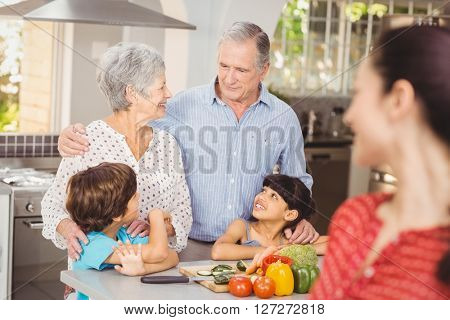 Happy family talking in kitchen at home