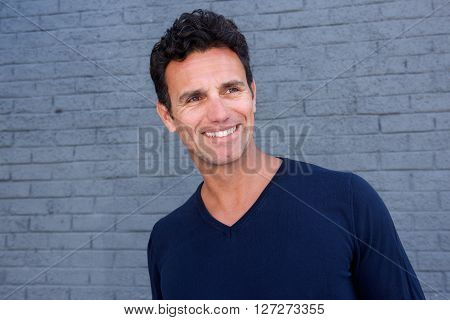 Smiling Older Man Standing Against Gray Wall