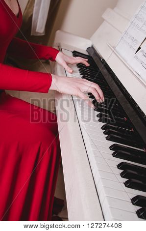 Hands and piano.Part of the body.hands on the white keys of the piano playing a melody.Women's hands on the keyboard of the pianoplaying the notes melody.Hands of young girlplays music on the piano