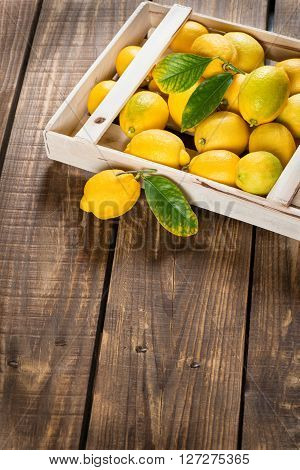 Juicy yellow lemons in crate on old wooden background with copy space.