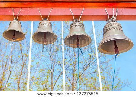 four bronze church bells hanging against blue sky