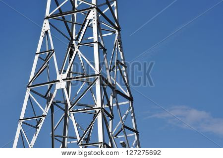 Electricity transmission line tower against blue sky