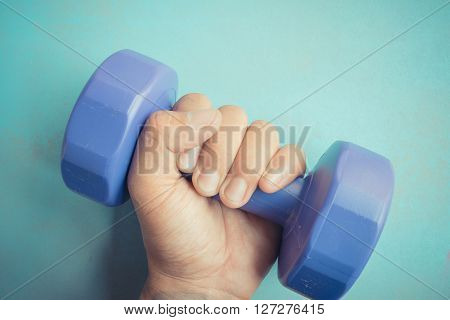 Dumb bell weight being held in one hand