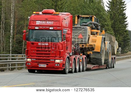 FORSSA, FINLAND - APRIL 23, 2016: Scania 164G transports heavy Volvo L350F wheel loader as wide load along road in South of Finland.
