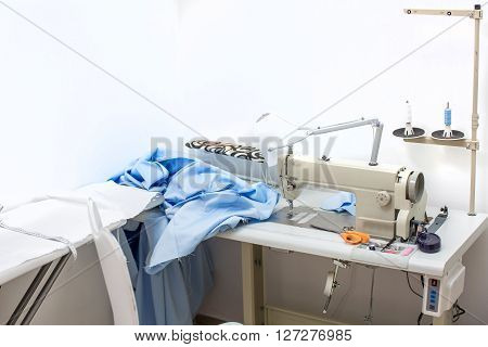 sewing machine and the blue cloth on the table. sewing kit. table seamstresses