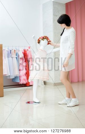 pretty young girl adjusts dress on the mannequin. baby dress on a mannequin