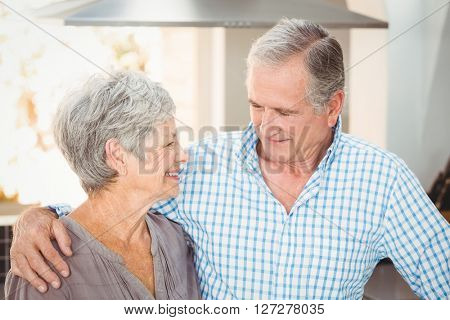 Happy senior couple looking at each other at home